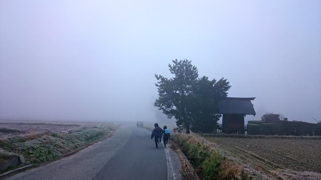 霧の中、元気に登校する子供たち