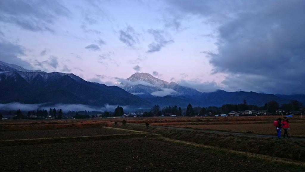 雲から顔を出し始めた有明山の前を歩く子供ら
