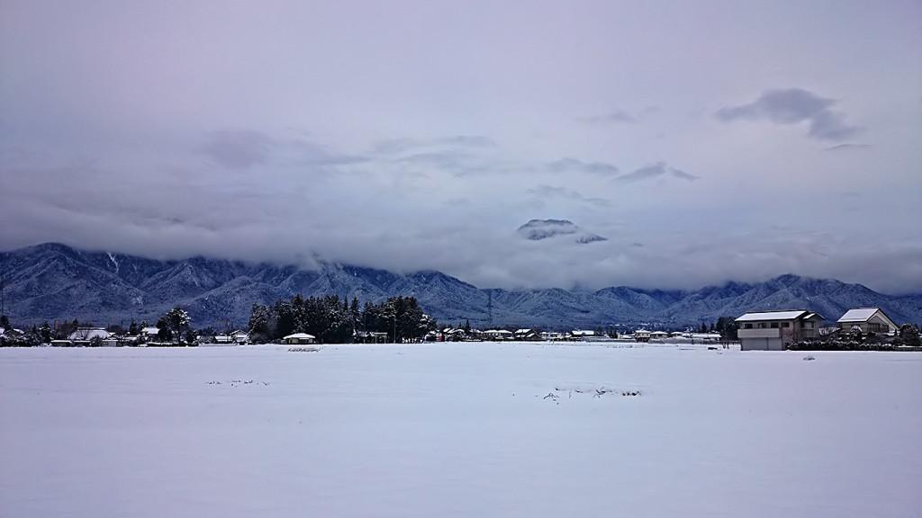 雪原と雲の白にサンドイッチになったような風景を有明山と。
