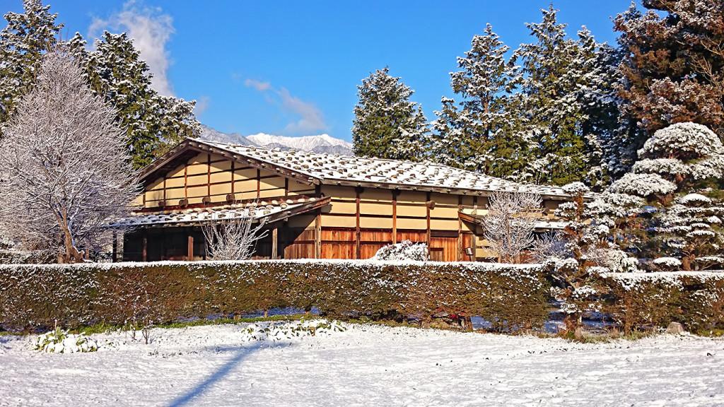 雪化粧した曽根原家住宅の上に頭を出している餓鬼岳