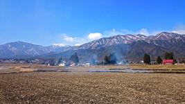 蝶ヶ岳を望む田んぼの土手の野焼き