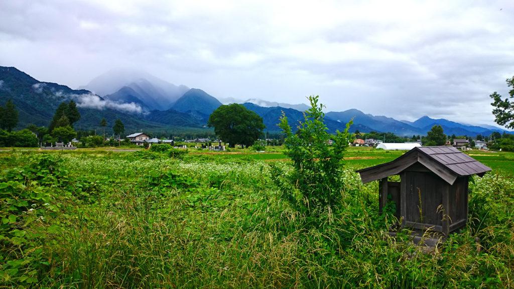 小さな祠と緑と雲がかかった山