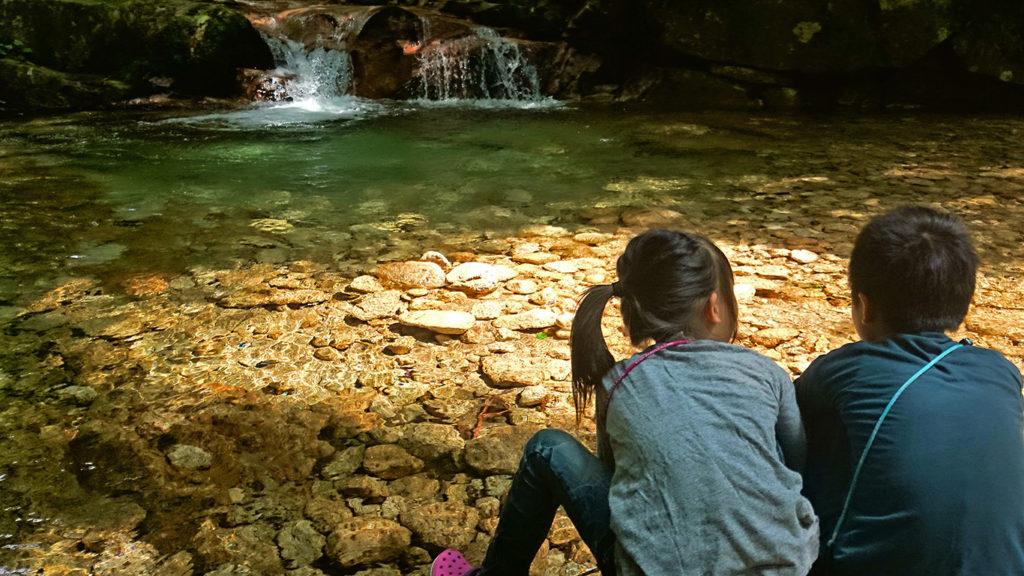 冷たい川の水を触ってみるチビッ子たち