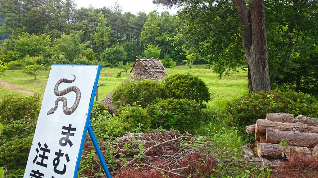 桜沢遺跡復元竪穴式住居前のマムシ注意の看板