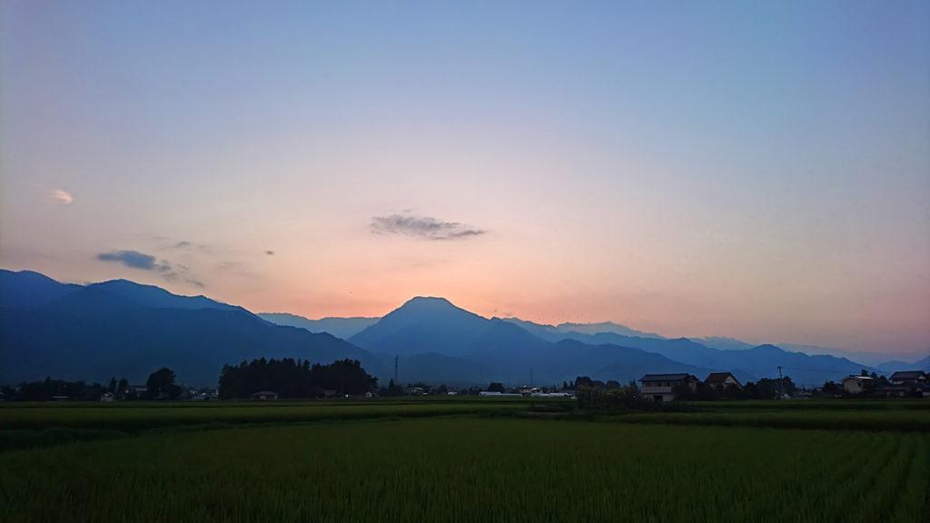 薄くピンク色に染まった空と有明山