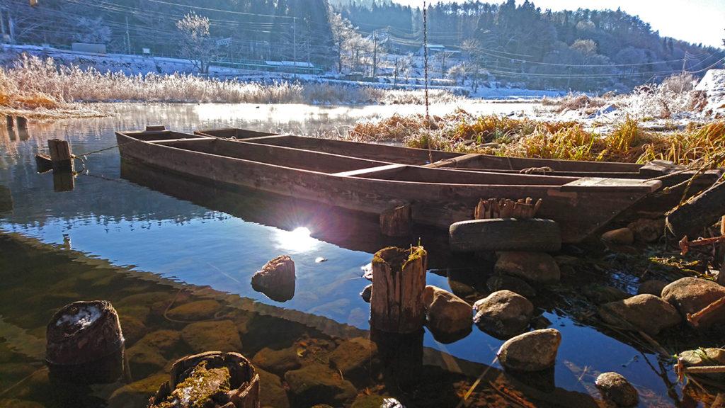 中綱湖に浮かぶボートと朝日の照り返し