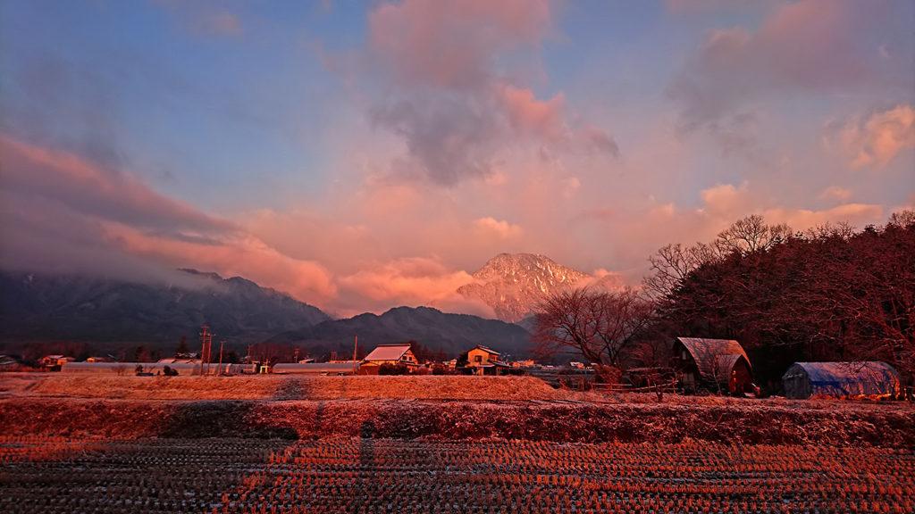 日の出頃の朝日を浴びる雪化粧した有明山