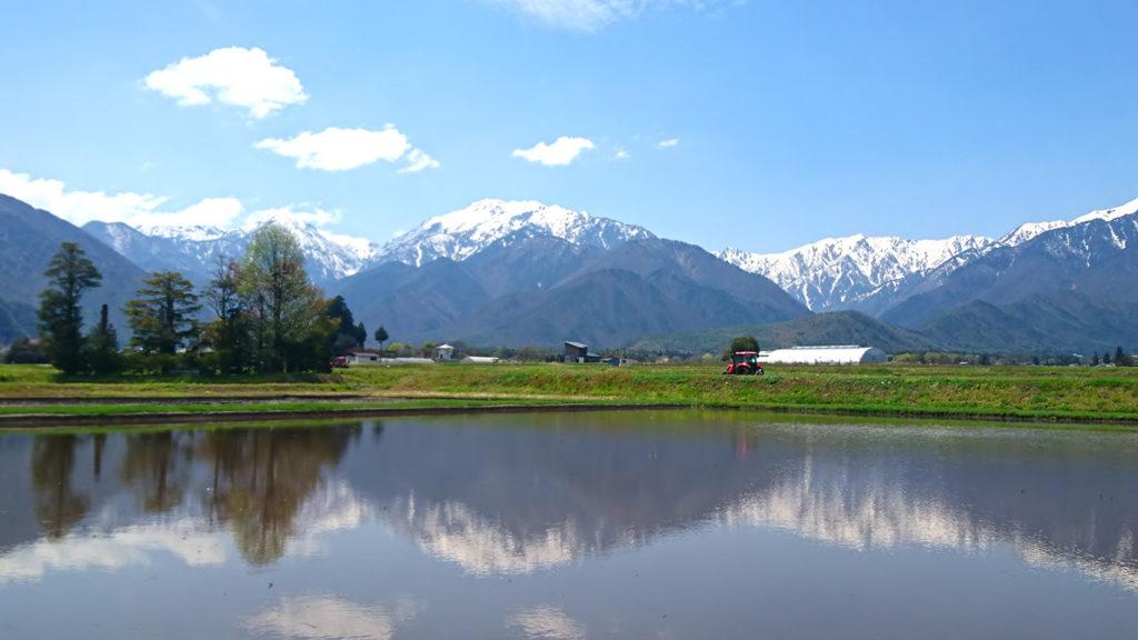 トラクターと田んぼと白く雪を被った山
